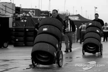 Crew members bring their tires to the pit area