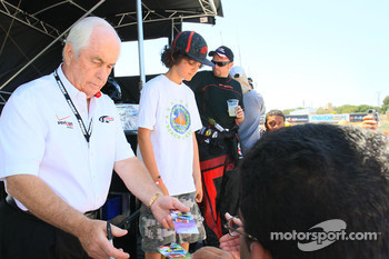 Roger Penske signs autographs for fans;