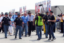 Richard Petty walks down Gasoline Alley under heavy security