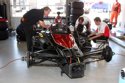 A crew member of the #98 CURB/Agajanian/Team 3G applies Jaques Lazier's name to the car