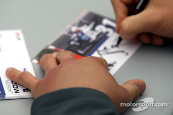 Jason Moore signs autographs with a swollen hand during the F2 driver autograph session