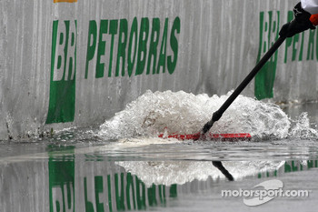 Mechanics sweep away the water from the pitlane