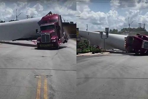 Videón, ahogy egy szélturbina lapátját szállító teherautó elakad egy vasúti átjáróban