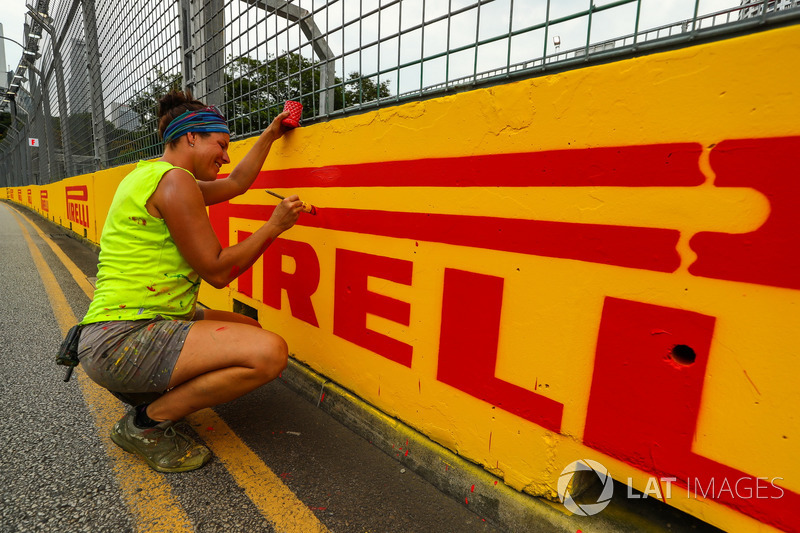 Una lavoratrice dipinge la barriera