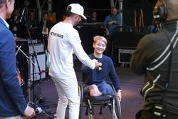 Lewis Hamilton, Mercedes AMG F1, on stage, injured British Formula 4 racer Billy Monger