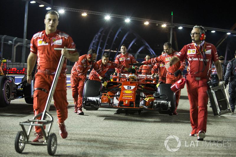 El coche de Sebastian Vettel, Ferrari SF70H, es empujado por miembros del equipo.
