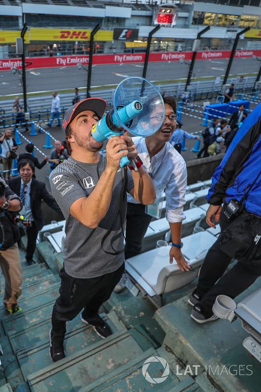 Fernando Alonso, McLaren, talks to the fans using a megaphone