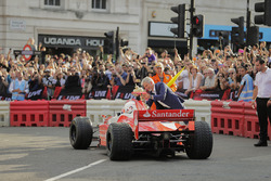 Jenson Button, McLaren, gives a passenger ride to Naomi Campbell in the 2 seater and Damon Hill offers the British Grand Prix trophy as a joke