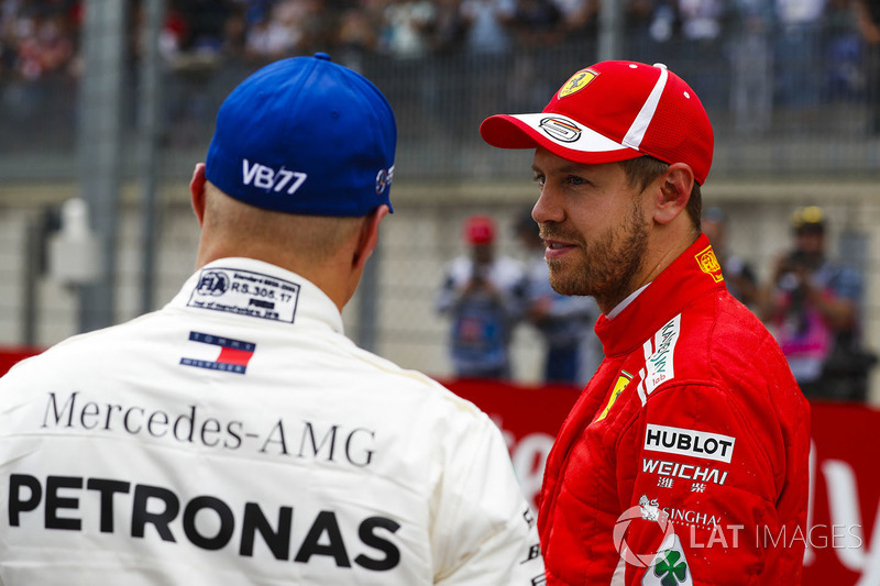Third place Sebastian Vettel, Ferrari, talks to pole sitter Valtteri Bottas, Mercedes AMG F1, after qualifying