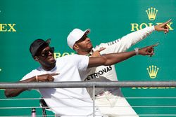 Usain Bolt performs his trademark lightning bolt pose with race winner Lewis Hamilton, Mercedes AMG