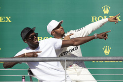 Usain Bolt performs his trademark lightning bolt pose with race winner Lewis Hamilton, Mercedes AMG F1, on the podium