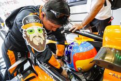 Un ingeniero ayuda a Fernando Alonso, McLaren MCL33, a amarrarse a su auto