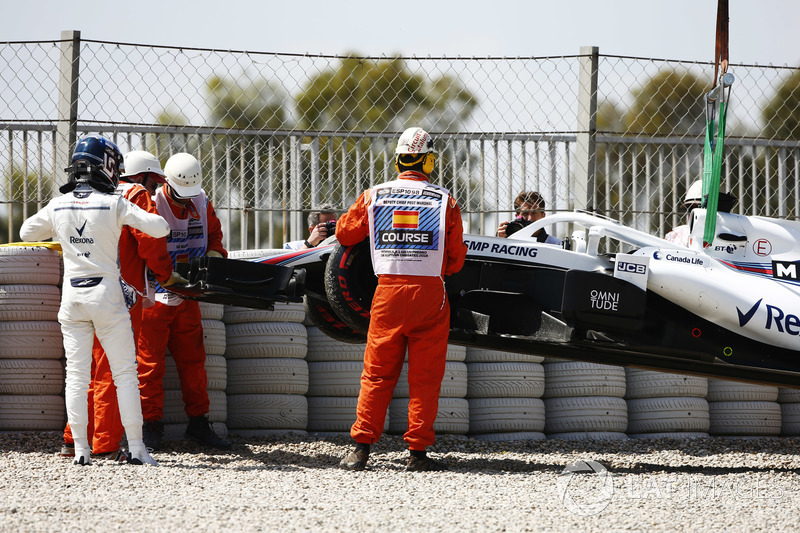 Lance Stroll, Williams Racing, studies his car after running into a gravel bed in FP1