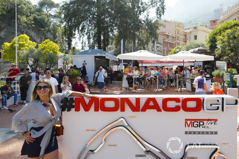 Une jeune femme pose à côté d'un panneau du Grand Prix de Monaco