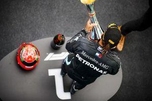 Lewis Hamilton, Mercedes-AMG F1, 1 ° posto, sul podio con il suo trofeo e il casco di Michael Schumacher
