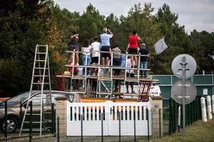 Fans ven la acción de la pista sobre la valla