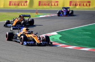 Carlos Sainz Jr., McLaren MCL34, leads Lando Norris, McLaren MCL34, and Pierre Gasly, Toro Rosso STR14