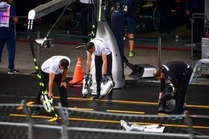 Mercedes mechanics attempt to dry the tarmac outside their garage
