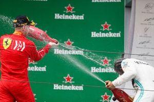 Sebastian Vettel, Ferrari, 3rd position, sprays Champagne at Lewis Hamilton, Mercedes AMG F1, 1st position