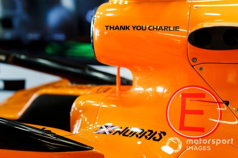Coche de Lando Norris, McLaren MCL34 en el garaje con un gráfico de agradecimiento en memoria de Charlie Whiting