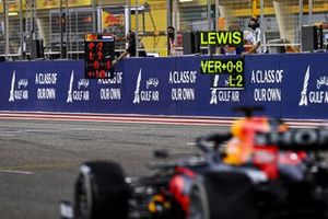Max Verstappen, Red Bull Racing RB16B, passes the pit boards
