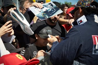 Lewis Hamilton, Mercedes AMG F1 signs a hat for a young fan