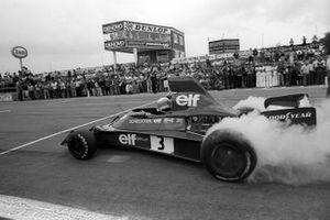 Jody Scheckter, Tyrrell 007 lights the tyres as he wins a pit stop tyre change competition against the McLaren team