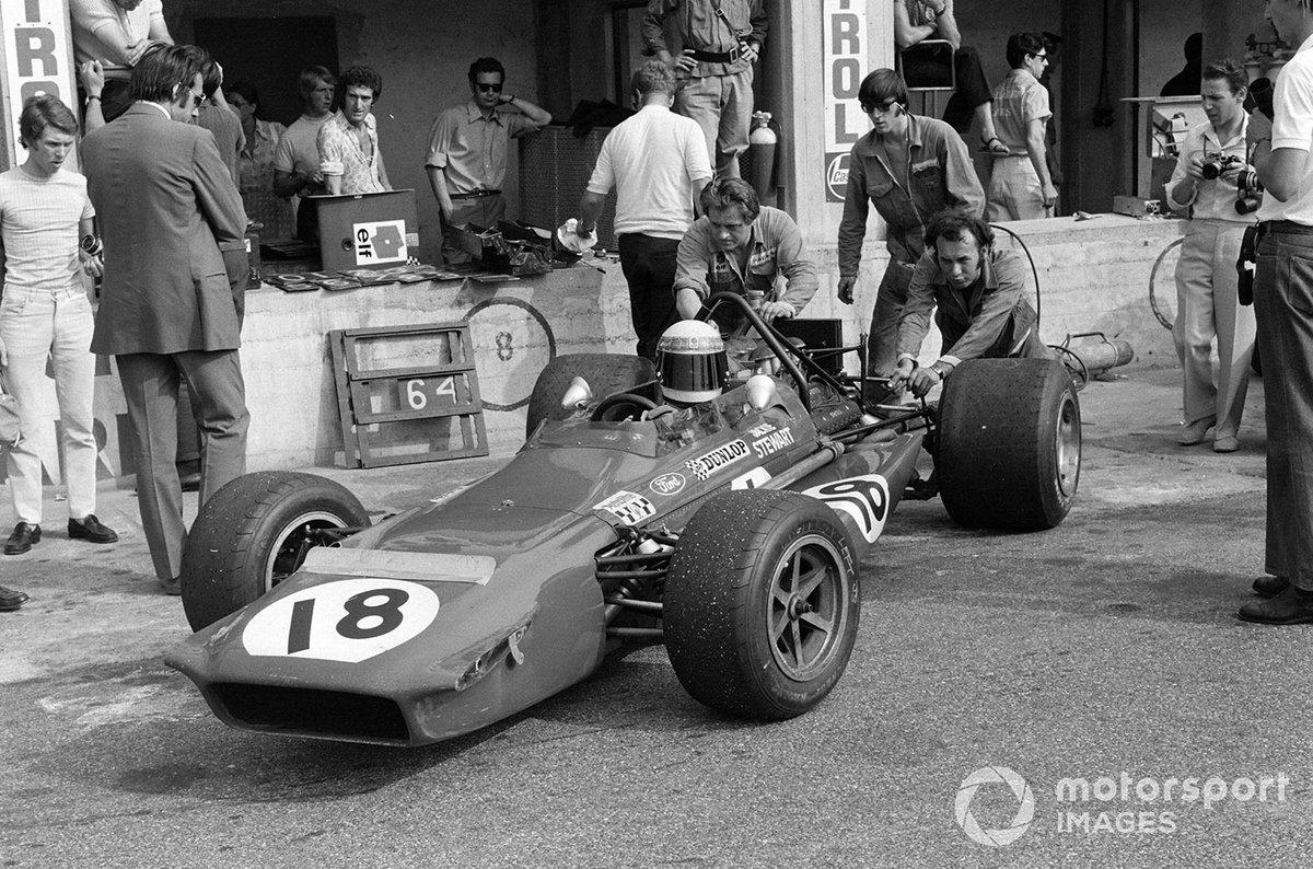Los mecánicos empujan a Jackie Stewart, March 701 Ford fuera de la caja de boxes