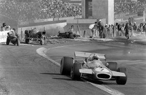 Jack Brabham, Brabham BT33 Ford, pasa a los oficiales que trabajan para retirar un coche quemado