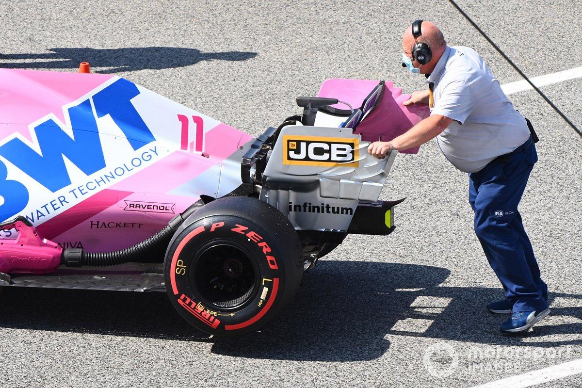 Un inspector de la FIA empuja el monoplaza de Sergio Pérez, Racing Point RP20 en Parc Ferme