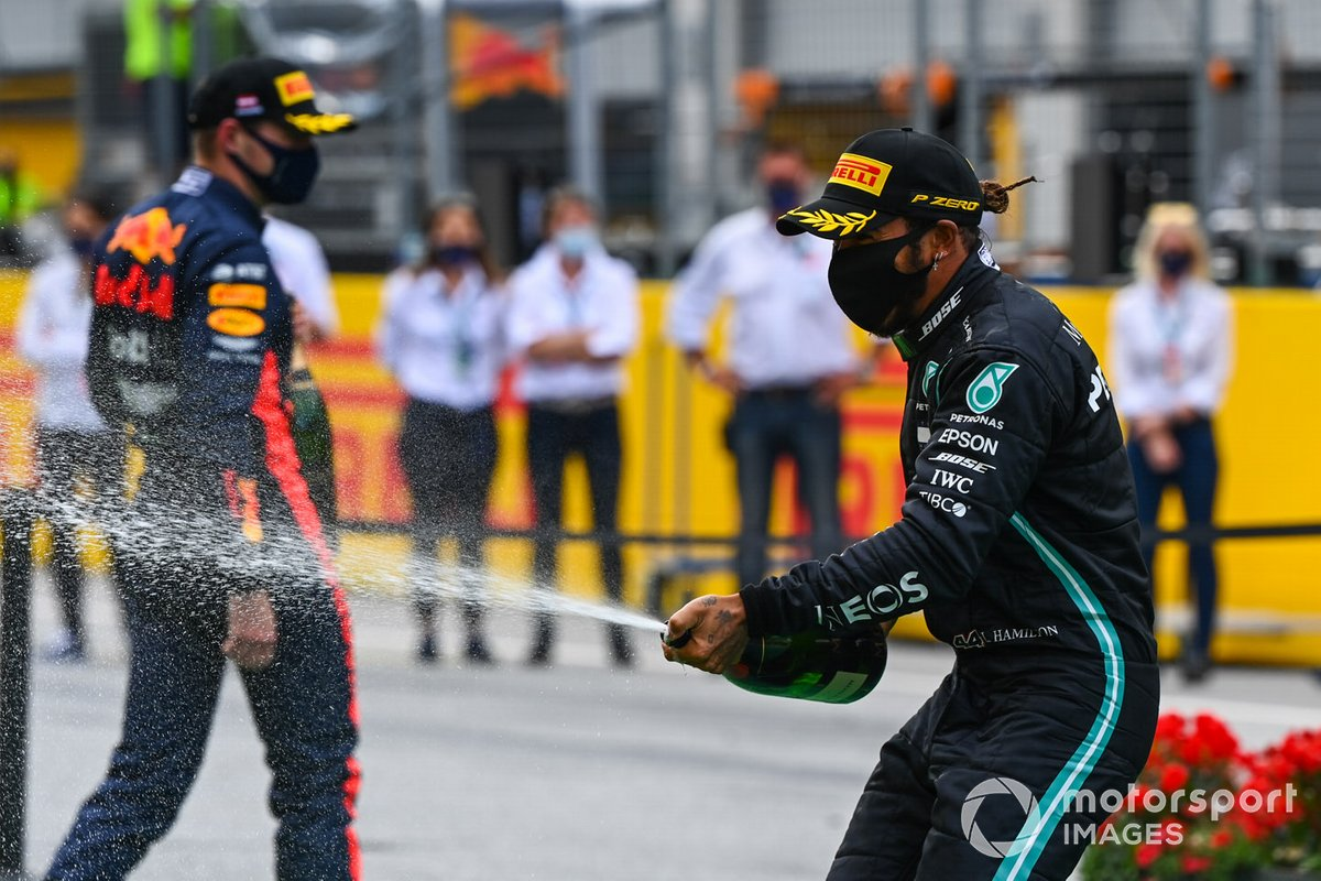 Lewis Hamilton, Mercedes-AMG Petronas F1, and Max Verstappen, Red Bull Racing spray champagne on the podium