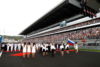 Drivers and dignitaries stand for the national anthem on the grid