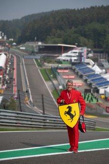 A man carries a Ferrari logo at Eau Rouge