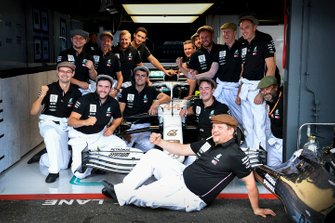 Mercedes AMG F1 mechanics pose for a photograph in front of the Mercedes AMG F1 W10 in the garage