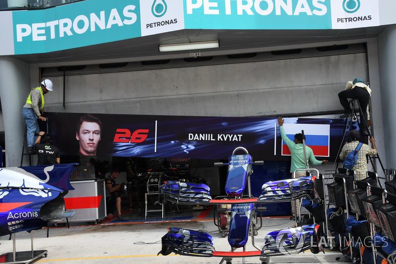 Рабочие снимают баннер с изображением Даниила Квята с гаража Toro Rosso в Малайзии