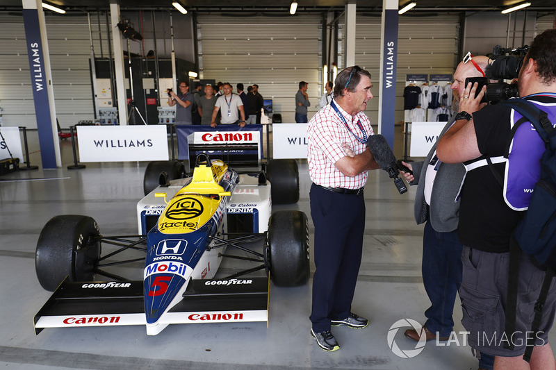 Nigel Mansell is interviewed next to a Williams FW11 Honda
