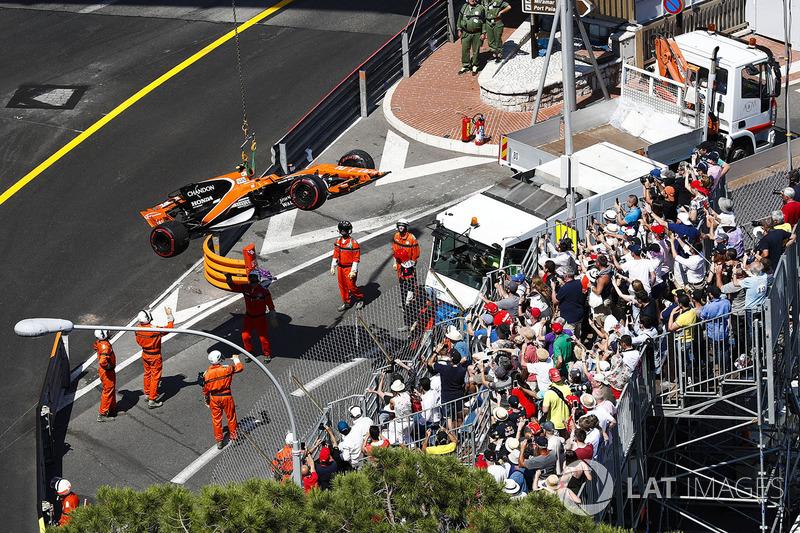 Oficiales de pista mueven el coche de Stoffel Vandoorne, McLaren MCL32