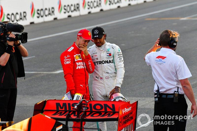 Sebastian Vettel, Ferrari, e Lewis Hamilton, Mercedes AMG F1, osservano il retro della Ferrari di Vettel, dopo le Qualifiche