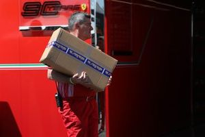 Un membro del team Ferrari con una scatola consegnata da Dallara