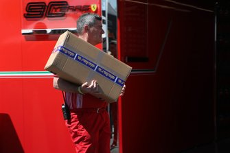 A Ferrari crew member with a box delivered from Dallara
