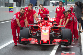 Des mécaniciens Ferrari poussent une Ferrari SF71H avec la nouvelle livrée