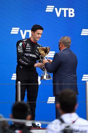 The Mercedes team representative receives the Constructors trophy