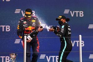 Max Verstappen, Red Bull Racing, 2e plaats, wordt door Lewis Hamilton, Mercedes, 1e plaats, op het podium bespoten met Champagne