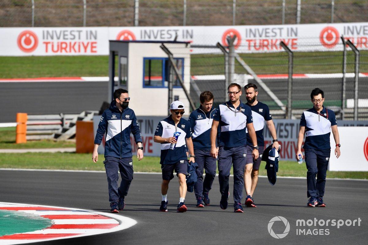 Yuki Tsunoda, AlphaTauri, walks the track with members of his team