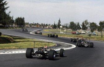 Jo Siffert, Lotus 49B-Ford Cosworth sigue a través de The Esses en la vuelta de apertura