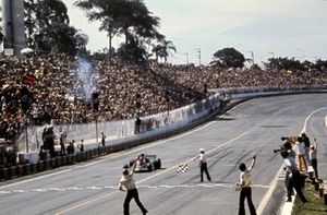 Emerson Fittipaldi, Lotus 72D crosses the line to become winner of the first Brazilian GP cheered on at trackside by Colin Chapman, Lotus Team Owner
