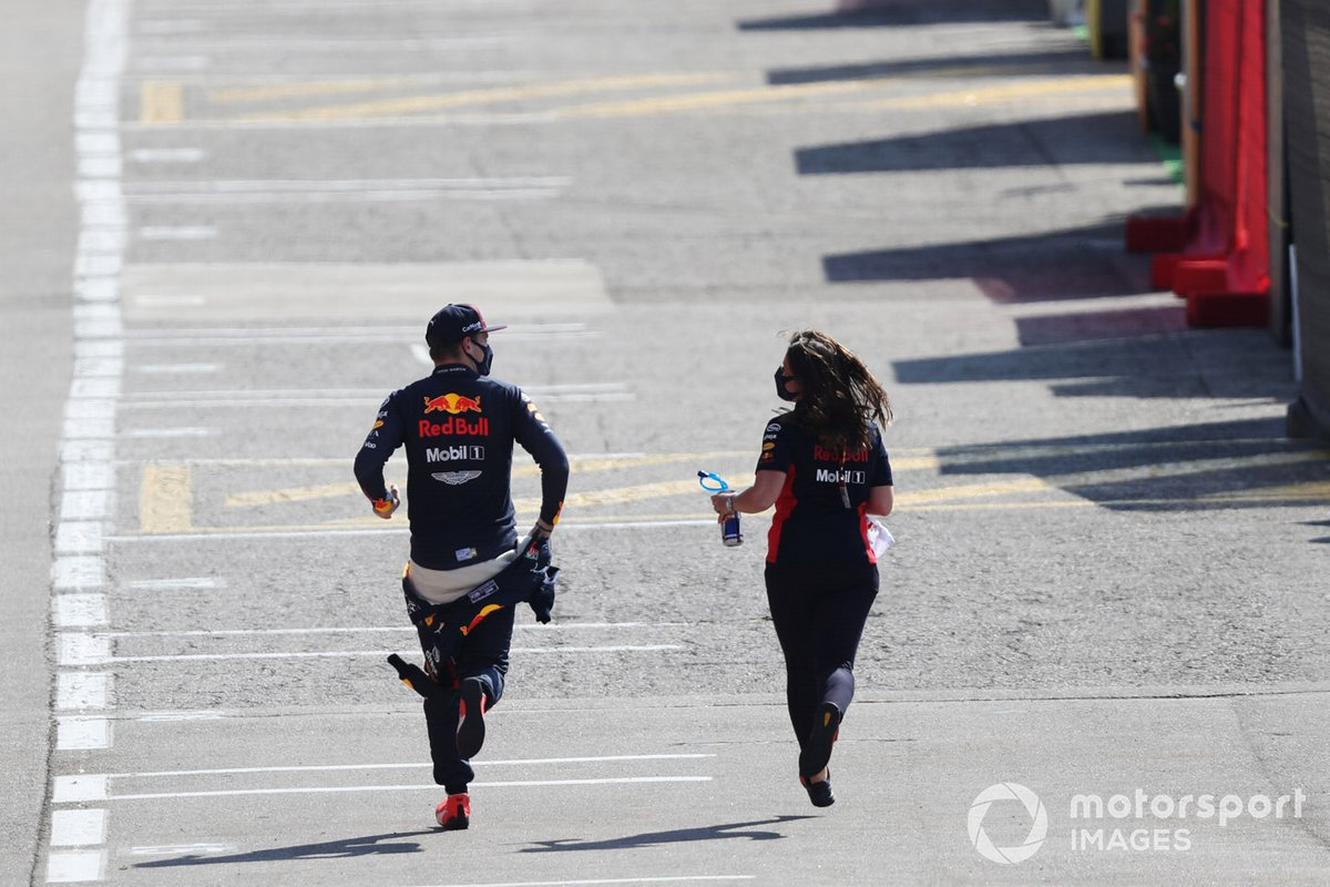 Макс Ферстаппен и сотрудница Red Bull Racing бегут по паддоку