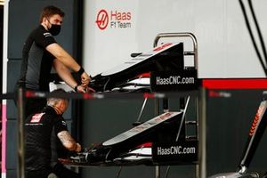 Nose cones and front wings of the Romain Grosjean Haas VF-20 are worked on by a team member