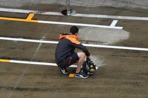 Mclaren team dry the pit lane