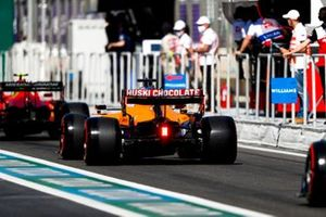 Carlos Sainz Jr., Ferrari SF21, and Daniel Ricciardo, McLaren MCL35M, in the queue to leave the pits